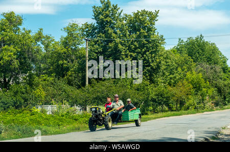 Buky, Ukraine - July 21, 2019: Two men and a boy ride a minitractor on the road in the countryside - Stock Photo