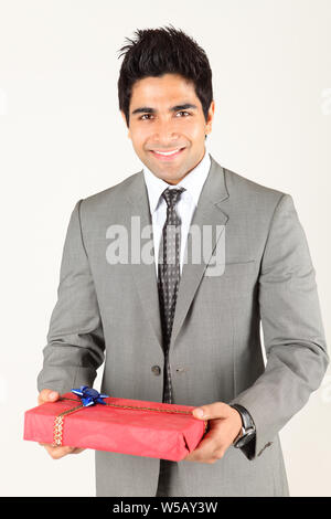 Businessman holding a gift box - Stock Photo