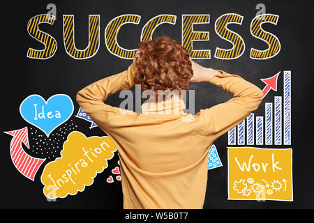 Kid looking at success inscription hand drawing sketch analytics charts on blackboard background - Stock Photo