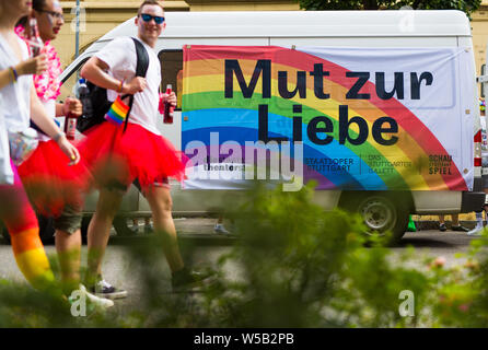 Stuttgart, Germany. 27th July, 2019. At the Christopher Street Day (CSD) parade, participants walk through downtown Stuttgart and past a banner with the inscription 'Courage to Love'. The political parade stands for the rights of gays, lesbians, bisexuals and transgender people under the motto 'Courage to Freedom'. Credit: Christoph Schmidt/dpa/Alamy Live News - Stock Photo