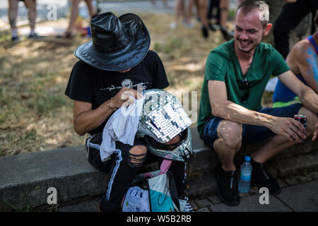 Stuttgart, Germany. 27th July, 2019. A participant in the Christopher Street Day (CSD) parade polishes a decorated motorcycle helmet. The political parade stands for the rights of gays, lesbians, bisexuals and transgender people under the motto 'Courage to Freedom'. Credit: Christoph Schmidt/dpa/Alamy Live News - Stock Photo