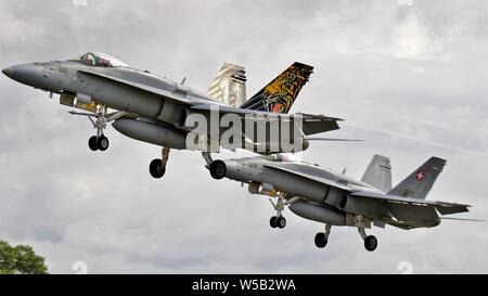 2 Swiss Air Force McDonnell Douglas F/A-18C Hornets arriving at RAF Fairford for the 2019 Royal International Air Tattoo - Stock Photo