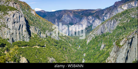View of Yosemite Valley with Merced river flowing through evergreen forests and Bridalveil Falls visible in the background; Yosemite National Park, Si - Stock Photo