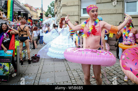 Stuttgart, Germany. 27th July, 2019. A participant in the Christopher Street Day (CSD) parade is walking through the city centre with a donut-shaped floating tyre. The political parade stands for the rights of gays, lesbians, bisexuals and transgender people under the motto 'Courage to Freedom'. Credit: Christoph Schmidt/dpa/Alamy Live News - Stock Photo