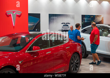 Valencia, Spain - July 21, 2019: Two buyers of a Tesla Model S electric car on display at Valencian Tesla store . Ecology friendly vehicle. - Stock Photo