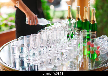 The waiter pours champagne on the buffet table. - Stock Photo