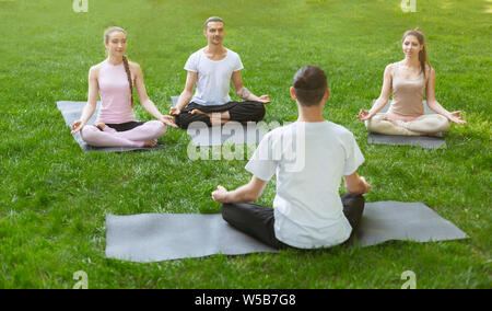 Young sporty people practicing yoga lesson with instructor - Stock Photo