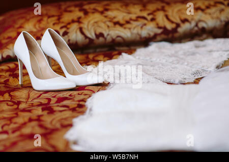 Wedding dress lying on a bed in bedroom. Bridal fees - Stock Photo