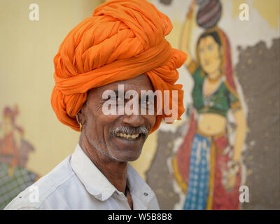 Indian Rajasthani man with an orange Rajasthani turban (pagari) poses for the camera in front of a mural. - Stock Photo