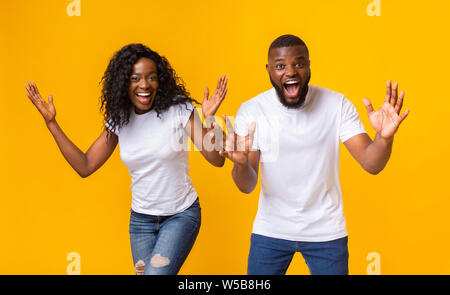 Shocked afro couple with hands wide open - Stock Photo