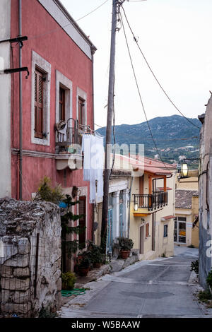 Narrow paved street with traditional greek houses in Archanes, Crete Island, Greece - Stock Photo