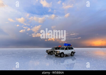 Two off-road vehicles stand on the salt flat of Uyunu at amazing sunset - Altiplano,  South America. - Stock Photo