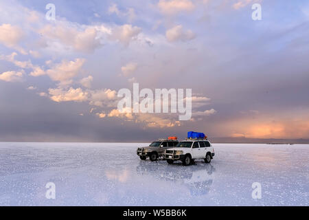 Two off-road vehicles stand on the salt flat of Uyunu - Altiplano,  South America. Photo does not noise or lens dust. It is pieces of salt. - Stock Photo