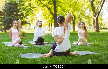 Group of people practicing yoga, sitting in Cow Face exercise - Stock Photo