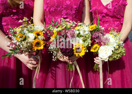 Three bridesmaids in lilac lace dresses with bouquets of fresh summer flowers, selective focus - Stock Photo