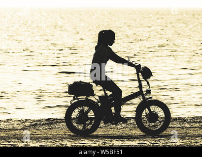 girl on an electric bike on beach - Stock Photo