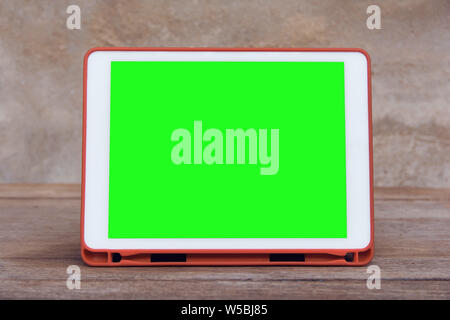 Mockup image of  White tablet pc with blank green desktop screen on wooden table - Stock Photo