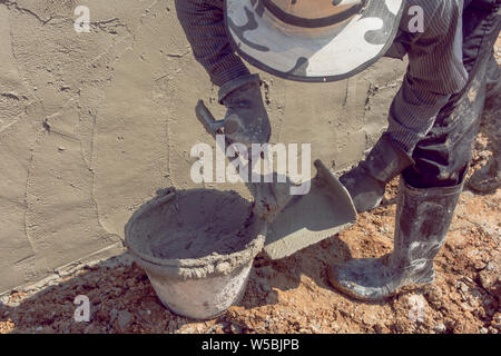 Construction workers plastering building wall using cement plaster - Stock Photo