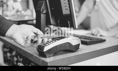 Shopper does payment using smartphone. NFC technology in the store - Stock Photo