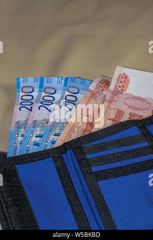 five and two thousand rubles banknotes, in a blue wallet, on white leader surface - Stock Photo