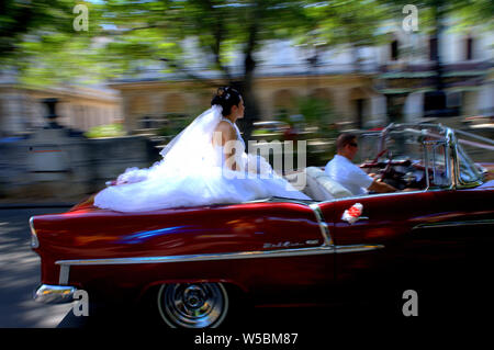 Bride rides along the street of Havana, Cuban in a classic convertible on her wedding day. - Stock Photo