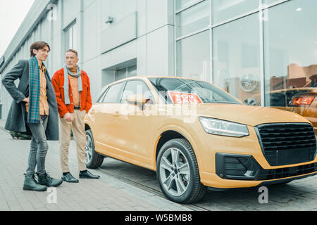 Man buying his son a new car. - Stock Photo