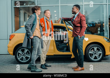 Two men talking to a car dealer after buying automobile. - Stock Photo