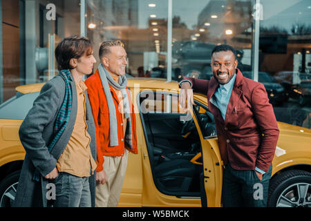 Happy car dealer selling automobile to a family. - Stock Photo
