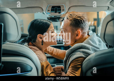 Husband and wife smiling before kissing in the car. - Stock Photo
