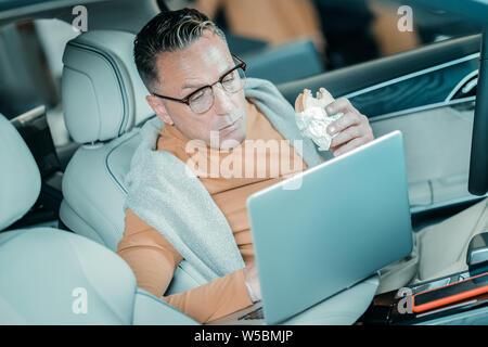 Man eating waiting for his wife in the car. - Stock Photo