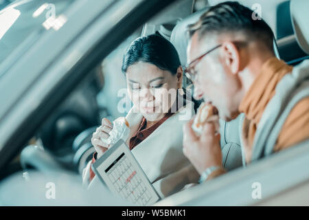 Husband and wife having lunch in the car. - Stock Photo