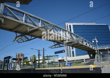 Pedestrian bridge over train track line at city station. - Stock Photo