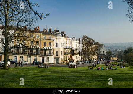 People relaxing and enjoying the green space of SIon Hill alongside Clifton Suspension Bridge and the Georgian properties of Clifton village, Bristol, - Stock Photo