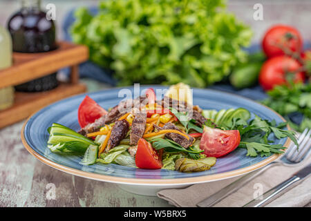 Juicy Beef Sirloin Steak Salad with roasted tomatoes, feta cheese and green vegetables in a blue plate. healthy food - Stock Photo