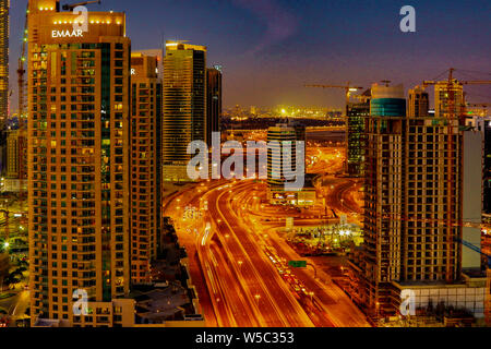 DUBAI, UAE, MAR 22, 2018: Traffic streams on a highway through town, running past skyscrapers - Stock Photo