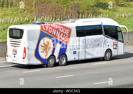 Bus transport for Olympique Lyonnais French football club based in Lyon France with logo on team coach seen driving along M25 UK motorway England UK - Stock Photo