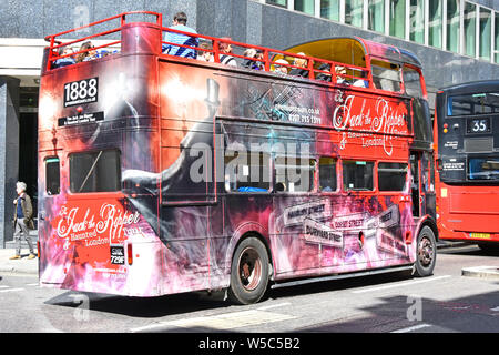 Historical Jack the Ripper open top double decker sightseeing tour bus covered with suitable graphics top deck with tourists & guide England London UK - Stock Photo