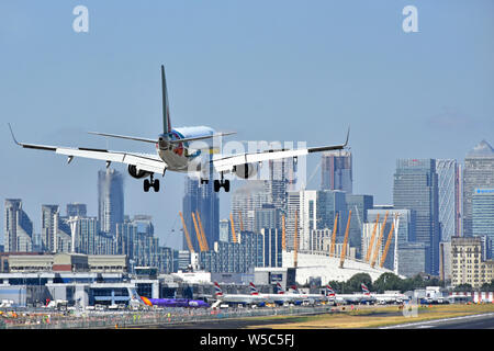 Alitalia airplane landing London City Airport Newham with O2 arena & Canary Wharf London Docklands cityscape skyline beyond Tower Hamlets England UK - Stock Photo