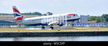 British Airways plane landing at London City Airport BA Cityflyer Embraer 190SR G-LCYR burning the rubber tyres upon touchdown in London Docklands UK - Stock Photo