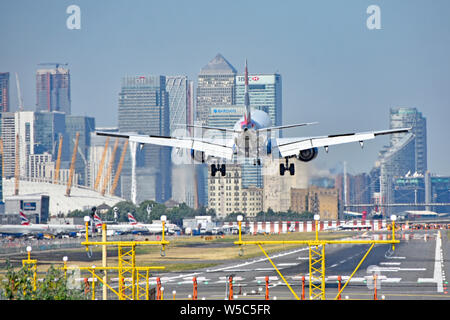 British Airways airplane landing London City Airport Newham with O2 arena & Canary Wharf in London Docklands skyline beyond Tower Hamlets England UK - Stock Photo