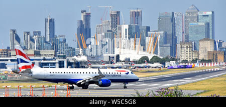 British Airways plane moving onto London City Airport runway for taking off landmark skyscraper buildings in cityscape skyline Canary Wharf beyond UK - Stock Photo
