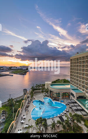 Sunset over the butterfly-shaped swimming pool of Loisir Hotel and the sea of Sumiyoshi district of Naha City in Okinawa island.