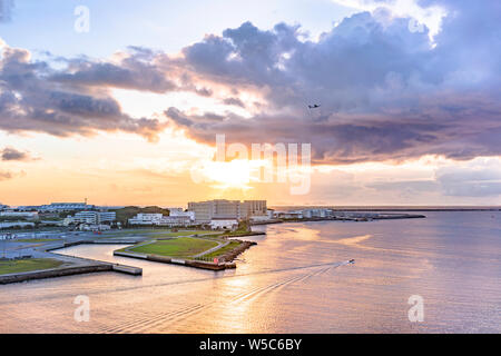 airplane flying over the sunset  sea in Sumiyoshi district of Naha CIty in Okinawa island from the Loisir Hotel