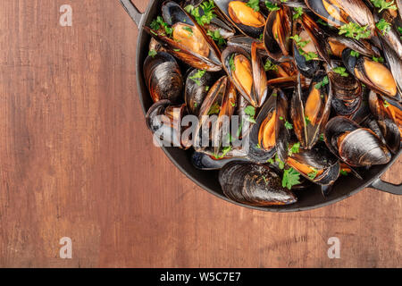 Marinara mussels, moules mariniere, cooked, in a pan, on a dark rustic wooden background with copy space, overhead close-up shot - Stock Photo
