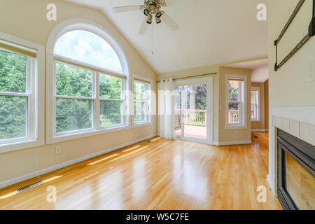 A empty undecorated dining room with many windows. - Stock Photo