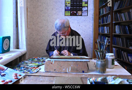 An artist who is still living at Chernobyl (city) is painting in his studio. Chernobyl, Cernobyl Exclusion Zone, northern Ukraine, Europe - Stock Photo