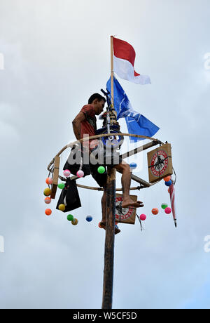 Banda Aceh, Indonesia - August 17, 2017: Celebrated the 70th anniversary of Independence. Man teams try to climb to the top of greased pole. - Stock Photo
