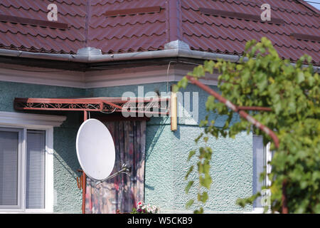 Television satellite receiver antenna on a house in a village in rural Romania - Stock Photo