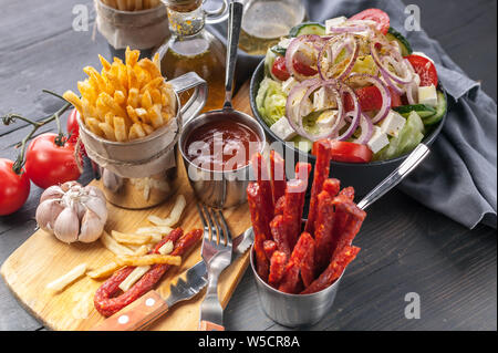 Homemade French Fries and Greek Salad. Onions, garlic, smoked sausages, tomato sauce, fork and spoon on a dark wooden table. - Stock Photo