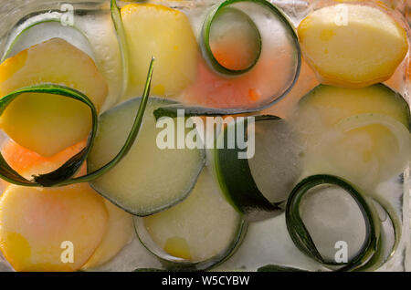 Background  skin and piece of  fresh szucchini   in ice   cube with air bubbles - Stock Photo